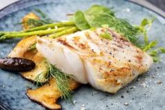 Gebratenes Kabeljau Fisch Filet mit grünen Spargel und Pilzen als closeup auf einem Teller