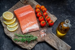 Raw salmon filet with paper with salt, peppers, lemon, thyme Olive oil and rosemary on over dark stone background, wild atlantic fish . Creative layout made of fish, top view, flat lay